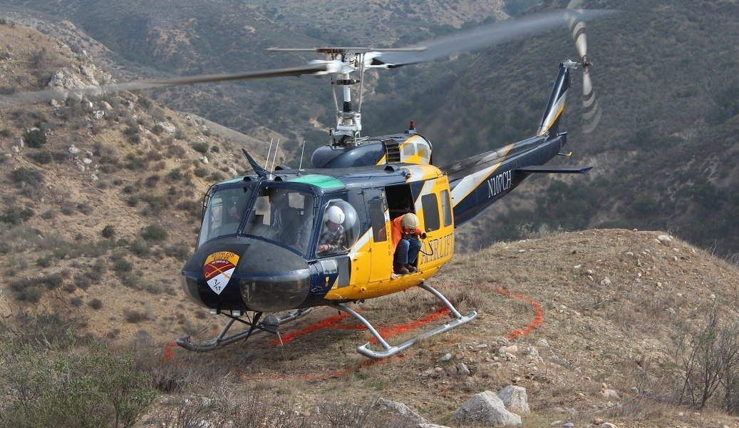 Vince Weatherby exits a helicopter in a remote mountain landing pad in California.